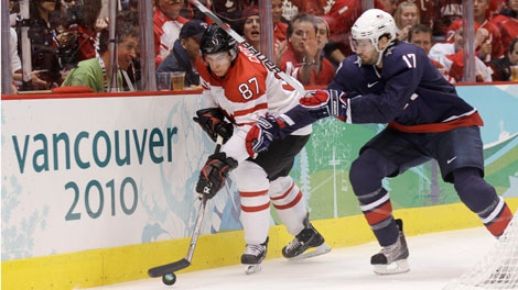 Canada's Sidney Crosby (87) moves the puck past USA's Ryan Kesler (17) in the first period of the men's gold medal ice hockey game at the Vancouver 2010 Olympics in Vancouver, British Columbia, Sunday, Feb. 28, 2010. (AP Photo/Matt Slocum)