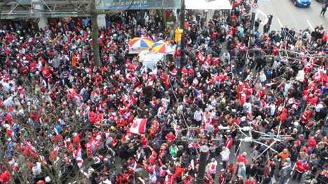 Thousands of hockey fans crowd onto the corner of Robson and Burrard streets in downtown Vancouver after Team Canada defeated Team USA in the gold medal men's hockey game on Sunday, Feb. 28, 2010. (Darcy Wintonyk for ctvbc.ca)