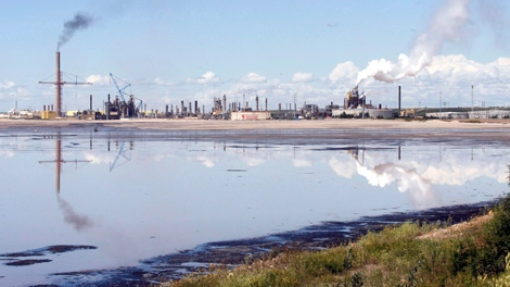 A tailings pond reflects the Syncrude oilsands mine facility near Fort McMurray, Alta., Wednesday, July 9, 2008. (Jeff McIntosh / THE CANADIAN PRESS)