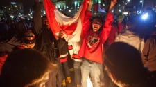 Team Canada Hockey fans celebrate by standing in the centennial flame on Parliament Hill in Ottawa on Sunday, Feb. 28, 2010 following Canada's win over the United States in overtime to take gold at the 2010 Vancouver Winter Olympic Games. THE CANADIAN PRESS/Pawel Dwulit