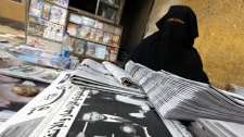 "An Egyptian newspapers vender wearing a niqab, a veil that exposes only her eyes, sits in front of newspapers fronted by pictures of the inauguration of Barack Obama, in Cairo, Egypt, Wednesday, Jan. 21, 2009. Obama used a few words in his inaugural address to reach out to the Muslim world, saying the U.S. was seeking ""a new way forward, based on mutual interest and mutual respect."" (AP Photo/Amr Nabil)"