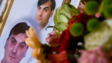 A picture of Robert Dziekanski lies next to a bouquet of flowers during a news conference in Vancouver. Oct. 25, 2007. (THE CANADIAN PRESS/Jonathan Hayward)