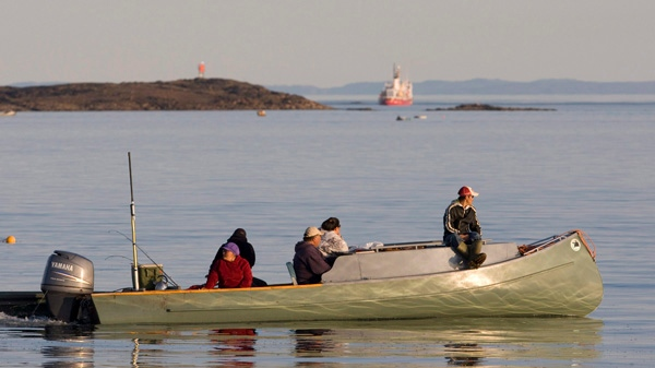 Inuit fishermen make their way along the bay in their boat in Iqaluit, Nunavut, Friday, August 21, 2009. (Jonathan Hayward / THE CANADIAN PRESS)