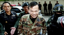 Escorted and guarded by Thai commandoes, Maj. Gen Khattiya Sawasdipol, center, a supporter of ousted Prime Minister Thaksin Shinawatra, is brought to criminal court Monday, March 8, 2010, in Bangkok. Khattiya and seven associates were arrested on Saturday on charges of illegal possession of firearms. (AP Photo/Apichart Weerawong)