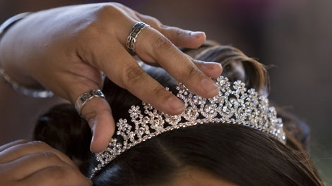 A tiara gets pinned in place before 15 young ladies from across the United States and Puerto Rico were given an opportunity celebrate their Quinceaneras at Disneyland Resort in Anaheim, Calif., Thursday, April 24, 2008. (AP Photo/Mark Avery)