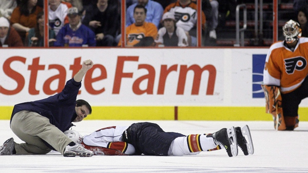 A person signals to the bench after checking on Florida Panthers forward David Booth, who was injured in the second period of an NHL hockey game against the Philadelphia Flyers, Saturday, Oct. 24, 2009. Booth suffered a concussion after a blindside head shot. (AP / Matt Slocum)