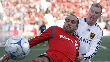 Toronto FC'a Dwayne De Rosario, left, battles for the ball against Real Salt Lake's Nat Borchers, right, during second-half MLS soccer action in Toronto on Saturday, Oct. 17, 2009. (THE CANADIAN PRESS/Nathan Denette)
