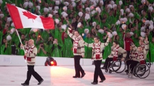 Canada's Jean Labonte carries the Canadian flag during the opening ceremonies of the Winter Paralympic Games in Vancouver, Friday, March 12, 2010. (CP/Jonathan Hayward)