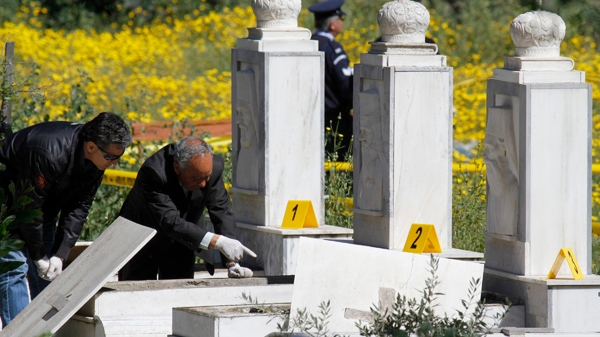Police officers inspect the graves of two Cyprus Archbishops at a cemetery in the capital Nicosia, Cyprus, Sunday, March 21, 2010. (AP / Petros Karadjias)