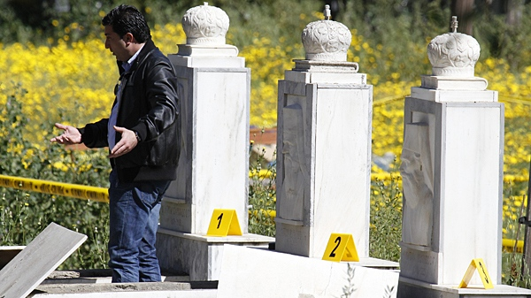 A police officer reacts as he stands near the graves of two Cyprus Archbishops at a cemetery in capital Nicosia, Cyprus, Sunday, March 21, 2010. (AP / Petros Karadjias)