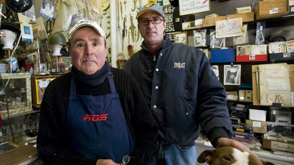 Abraham, left, and Ivan Botines with their dog Sasa pose for a photograph in their curiosity shop in Montreal, Friday, March 26, 2010 where they are selling a controversial bar of soap, allegedly made by the Nazi's with the remains of victims from the holocaust. (THE CANADIAN PRESS/Graham Hughes)