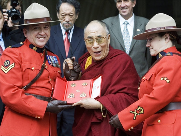 The Dalai Lama receives a gift from Royal Canadian Mounted Police Corporal Yvon Brault and Sgt. Monique Beauchamp upon his arrival on Parliament Hill, in Ottawa Monday Oct 29, 2007. (CP / Tom Hanson)