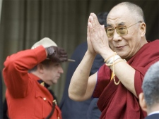 The Dalai Lama acknowledges followers as an RCMP officer salutes upon his arrival on Parliament Hill in Ottawa, Monday, Oct 29, 2007. (CP / Tom Hanson)