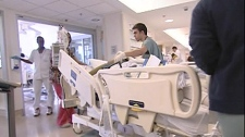 A patient is wheeled into the Montreal General Hospital's Intensive Care Unit. (March 29, 2010)