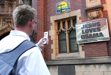 A pedestrian stops to take a photograph of a sign reading 'Jesus Loves Osama' outside of a church in Sydney, Australia. (AP / Paul Miller)