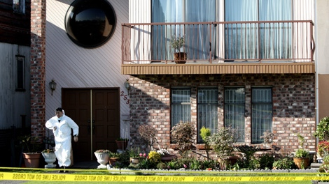 A police forensics investigator walks out of a house during a homicide investigation in Vancouver, B.C., on Wednesday March 31, 2010. Police in Vancouver are investigating the death of an infant at the same home where a baby's remains were found last year. (CP/Darryl Dyck)