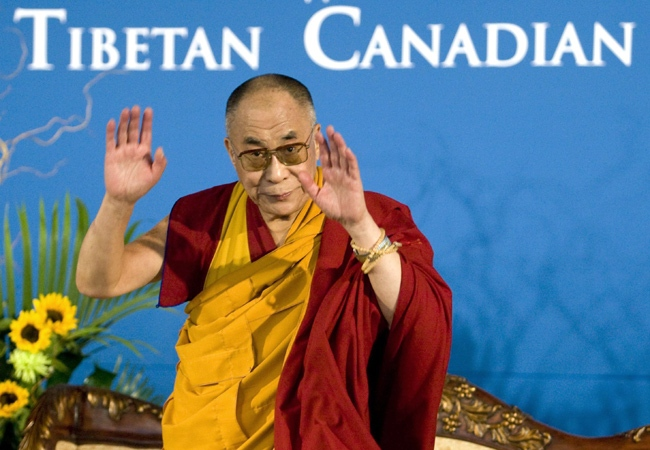 The Dalai Lama gestures to the audience as he arrives at a ceremonial blessing at the Tibetan Canadian Cultural Centre in Toronto on Wednesday, Oct.31, 2007. (CP / Adrian Wyld)