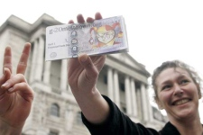 Demonstrators show fake banknotes depicting a jester with Wednesday's date, April 1, known as All Fools Day in various countries, as fellow demonstrators against the G20 gather to have a cup of tea in front of the Bank of England in central London, Tuesday, March 31, 2009.(AP Photo/Akira Suemori)