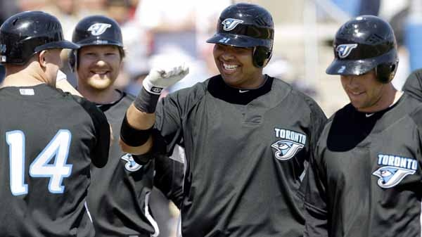 Toronto Blue Jays' Randy Ruiz, center, celebrates with teammates John Buck (14), Aaron Hill, right, and Adam Lind after he hit a grand slam against Detroit Tigers' Jeremy Bonderman during the first inning of a spring training baseball game, Sunday, March 7, 2010, in Dunedin, Fla. (AP Photo/Eric Gay)