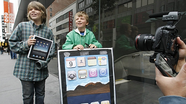 Milo Kahmey, left, 12, holds his new Apple iPad as his brother, Lyle Kahmey, right, 9, wears an iPad billboard after buying an iPad on the first day of Apple iPad sales at an Apple store in San Francisco, Saturday, April 3, 2010. (AP / Paul Sakuma)