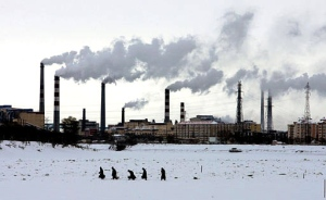 Residents walk across the frozen Songhua River in front of smoke stacks at Jiamusi, in China's northeast Heilongjiang province. China is the second largest emitter of greenhouse gases, after the U.S. (AP / Greg Baker)
