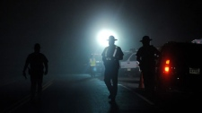 West Virginia State Police officers direct traffic in front of an entrance to the Massey Energy Co.'s Upper Big Branch mine in Montcoal, W.Va. in Raleigh County early Tuesday, April 6, 2010. (AP / Post-Gazette, Michael Henninger)