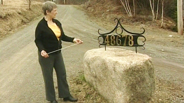 Earlene Busch indicates where the dead coyote was found at the entrance to her Cape Breton inn in this image taken from video.