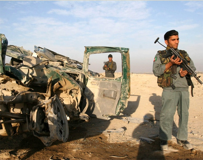 Afghan police men stand near a police vehicle damaged in an explosion in Chaprahar district IN Nangarhar province, eastern Afghanistan, Tuesday, Nov. 6, 2007. (AP / Rahmat Gul)