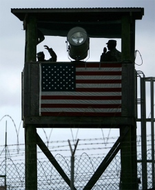 Guards sit in a tower overlooking Guantanamo Bay U.S. Naval Base, Cuba. This image has been reviewed and approved by U.S. Department of Defense. (AP / Brennan Linsley)