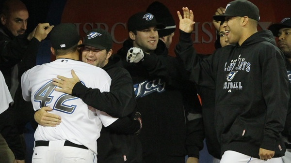 Toronto Blue Jays' Shaun Marcum hugs starting pitcher Dana Eveland as teammates Ricky Romero, right, and Brandon Morrow, second from right, celebrates Eveland's work against the Chicago White Sox during AL baseball action in Toronto on Thursday, April 15, 2010. (Darren Calabrese / THE CANADIAN PRESS)