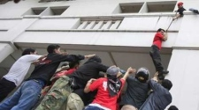 Anti-government leader Arisman Pongruanrong, in red, is helped by others as he flees arrest Friday, April 16, 2010, at a downtown Bangkok, Thailand, hotel. Arisman scaled down the facade of the hotel in downtown Bangkok into a waiting crowd of 'Red Shirt' supporters who then helped him into a car that drove away.(AP Photo/Wong Maye-E)