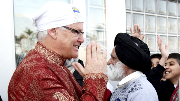 British Columbia Premier Gordon Campbell, left, greets people while attending the Vaisakhi parade in Vancouver, B.C., on Saturday April 10, 2010. (Darryl Dyck / THE CANADIAN PRESS)