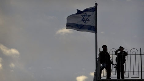 Israeli soldiers stand guard on a roof during a service marking Memorial Day at the Western Wall, Judaism's holiest site in Jerusalem's Old City, Sunday, April 18, 2010. Israelis marked Memorial Day starting Sunday evening in remembrance of the nation's fallen soldiers. (AP Photo/Sebastian Scheiner)