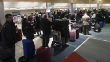 Passengers wait to check-in at midnite at St. John's International Airport, Sunday, April 18, 2010. (Ryan Remiorz / THE CANADIAN PRESS)