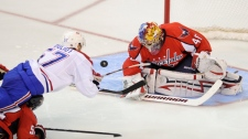 Montreal Canadiens left wing Benoit Pouliot (57) dives for the puck against Washington Capitals goalie Semyon Varlamov (40), of Russia, during the third period of Game 2 of the NHL hockey playoffs, Saturday, April 17, 2010, in Washington. (AP Photo/Nick Wass)