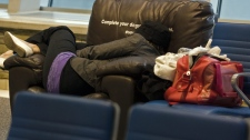 Emily Mantle from Calgary takes a nap at St. John's International Airport after flights were cancelled early Monday, April 19, 2010. (Andrew Vaughan / THE CANADIAN PRESS)