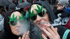 Brenna Richardson and Sam Buchan, right, of Surrey, B.C. smoke marijuana outside the Vancouver Art Gallery in downtown Vancouver, Tuesday, April 20, 2010. The event is to promote the use of marijuana in Canada. (CP/Jonathan Hayward)
