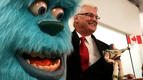 British Columbia Premier Gordon Campbell stands next to a figure of Sulley, from the Pixar movie Monsters Inc. while holding a Buzz Lightyear toy, from the movie Toy Story, during the opening of Pixar Canada in Vancouver, B.C., on Tuesday April 20, 2010. Pixar, a subsidiary of the Walt Disney Company, will make short films at the new studio. (CP/Darryl Dyck)