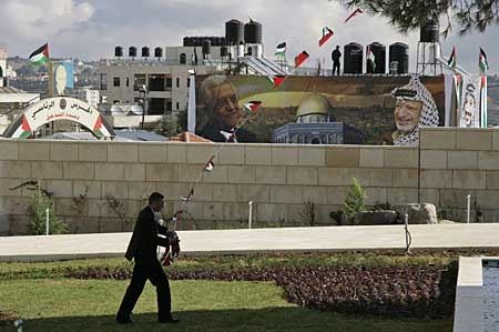 A Palestinian security officer collects flags set as decoration before a ceremony inaugurating late Palestnian leader Yasser Arafat's new grave at Palestinian President Mahmoud Abbas' headquarters in the West Bank city of Ramallah, Saturday, Nov. 10, 2007.(AP Photo/Maya Hasson)