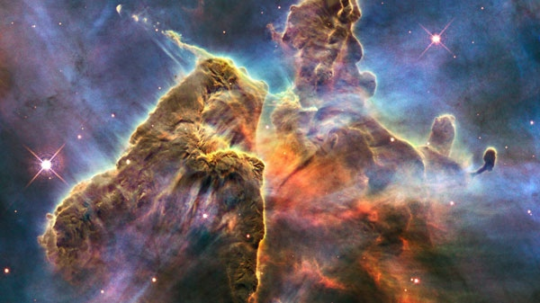 In this image provided by NASA, the Hubble Space Telescope captures the chaotic activity atop a three-light-year-tall pillar of gas and dust that is being eaten away by the brilliant light from nearby bright stars. (AP Photo/NASA)