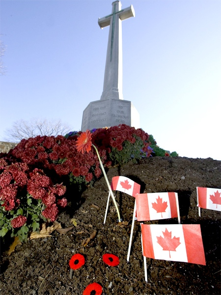 Canadian flags and poppies lay by the Croix du Souvenir following a Remembrance Day ceremony in Quebec City. (CP / Jacques Boissinot)