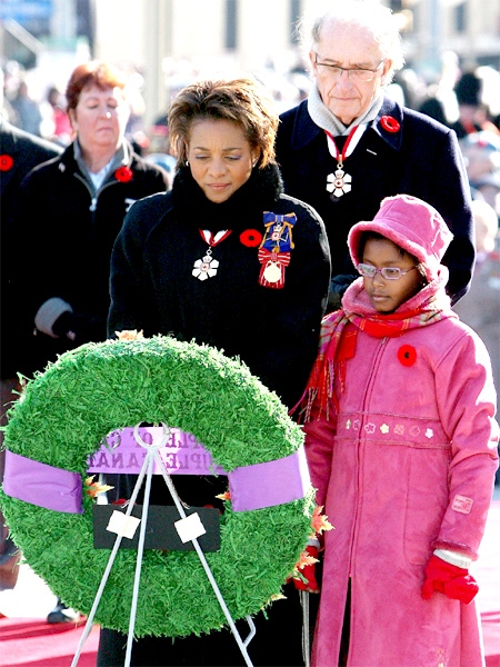 Michaelle Jean, Governor General of Canada, with her daughter Marie-Eden and husband Jean-Daniel Lafond, pauses for a moment after laying a wreath at the National War Memorial. (CP / Sean Kilpatrick)