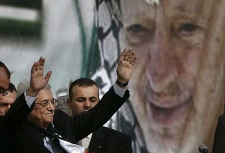Palestinian President Mahmoud Abbas, also known as Abu Mazen, left, backdropped by a portrait of late Palestinian leader Yasser Arafat, in the West Bank city of Ramallah, Sunday, Nov. 11, 2007. (AP Photo/Emilio Morenatti)