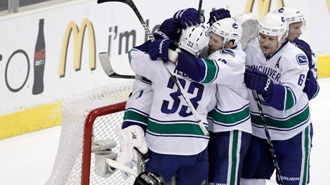 The Vancouver Canucks celebrate their win as Los Angeles Kings left wing Ryan Smyth skates off during Game 6 of a first-round NHL hockey Western Conference playoff series in Los Angeles, Sunday, April 25, 2010. Vancouver won 4-2. (AP Photo/Chris Carlson)