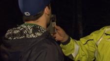A police officer admininsters a roadside breathalyzer test. (CTV)