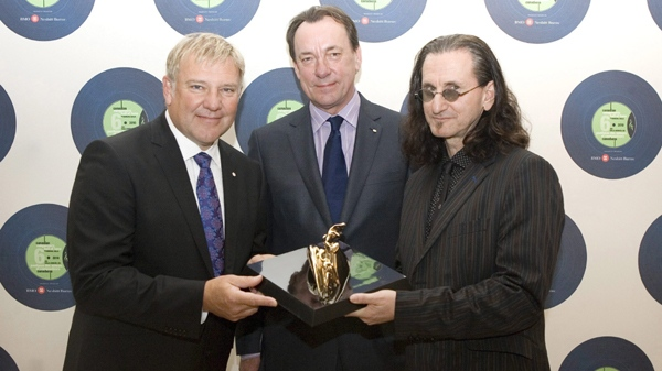 Alex Lifeson, left, Neil Peart, centre, and Geddy Lee of the band Rush pose with a trophy during a photo opportunity ahead of ceremony to induct them into the Canadian Songwriters Hall of Fame in Toronto on Sunday March 28, 2010. THE CANADIAN PRESS/Chris Young