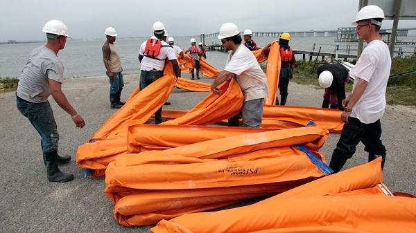 Workers load a boat with oil booms in Bay St. Louis, Miss., as they continue preparations to head off damage from an impending oil spill along the Gulf coast Friday, April 30, 2010. (AP / Dave Martin)