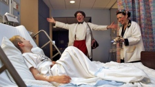 Clowns Stephen Ringold and Phyllis Capello, right, perform for Connor Moran, 7, during their Clown round at New York-Presbyterian's Morgan Stanley Children's Hospital in New York on December 1, 2006. (AP / Dima Gavrysh)