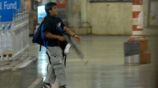 An armed Mohammed Ajmal Kasab walks at the Chatrapathi Sivaji Terminal railway station in Mumbai, India on Wednesday, Nov. 26, 2008. (AP / Mumbai Mirror, Sebastian D'souza)