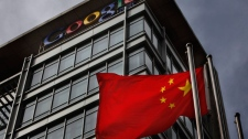 A Chinese flag blows in the air below the Google logo outside the Google China headquarters in Beijing Thursday, March 25, 2010.  (AP /  Gemunu Amarasinghe)